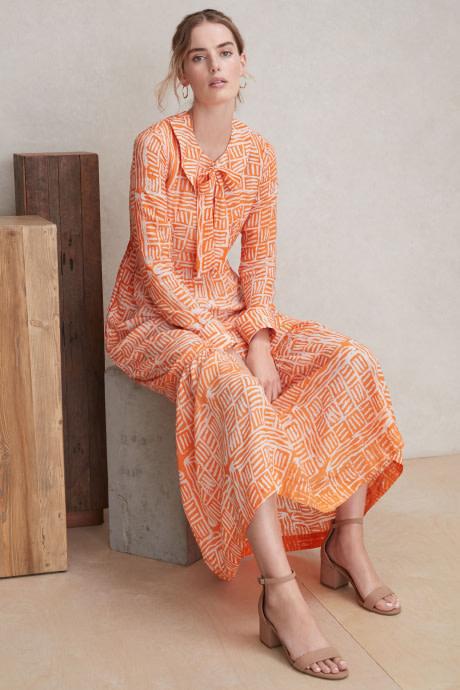 Model wearing Stitch Fix Elevate grantees women's orange and white print dress.