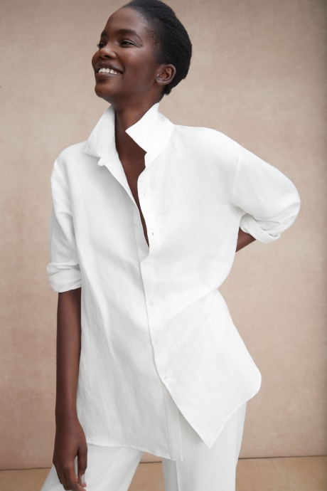 Model wearing Stitch Fix Elevate Chloe Kristyn women's white blouse with rolled sleeves and white pants.