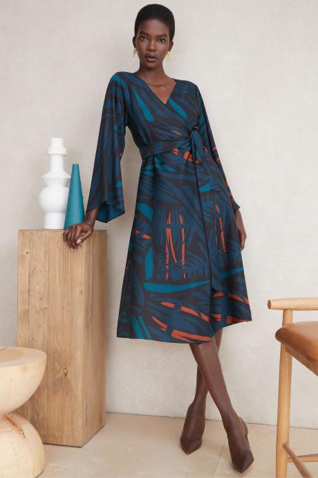 Model wearing Stitch Fix Elevate grantees women's blue print wrap dress.