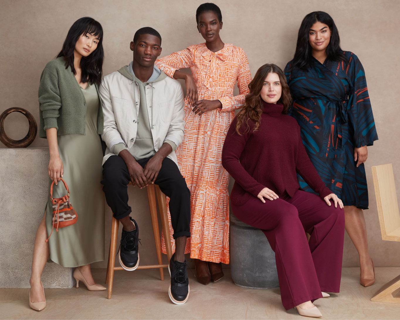 Models wearing Stitch Fix Elevate grantees clothing, including multicolor dresses, nude pumps and mens black shoes.