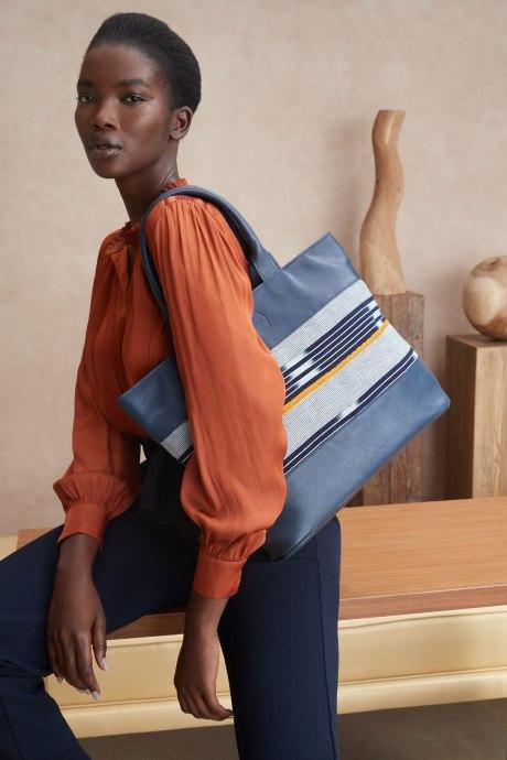 Stitch Fix Elevate grantees women's blue tote bag with orange and blue stripes.