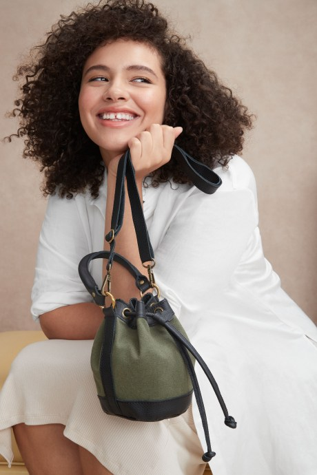 Model holding a small green and black drawstring bucket bag by Stitch Fix Elevate grantee.