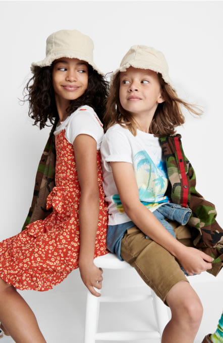 Models wearing Stitch Fix kids summer clothes including tees, hats, sneakers, red floral dress, khaki shorts and camo jacket.