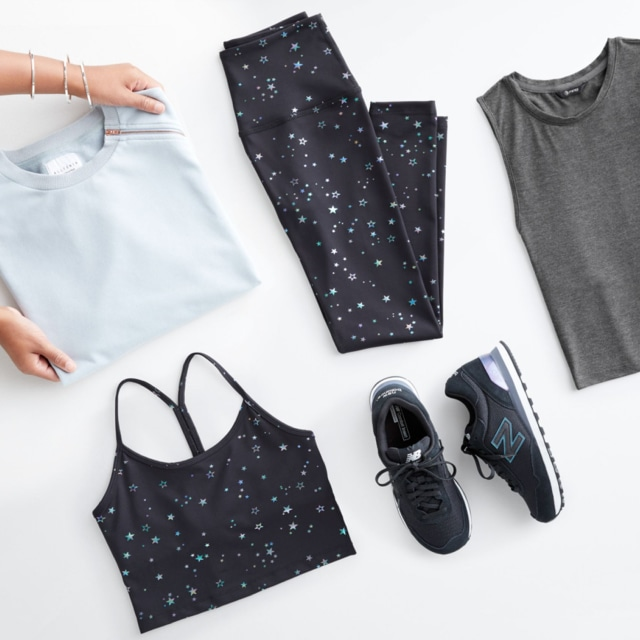 Folded Stitch Fix women's athleisure clothes including printed leggings and top, grey tank top, grey hoodie and sneakers.