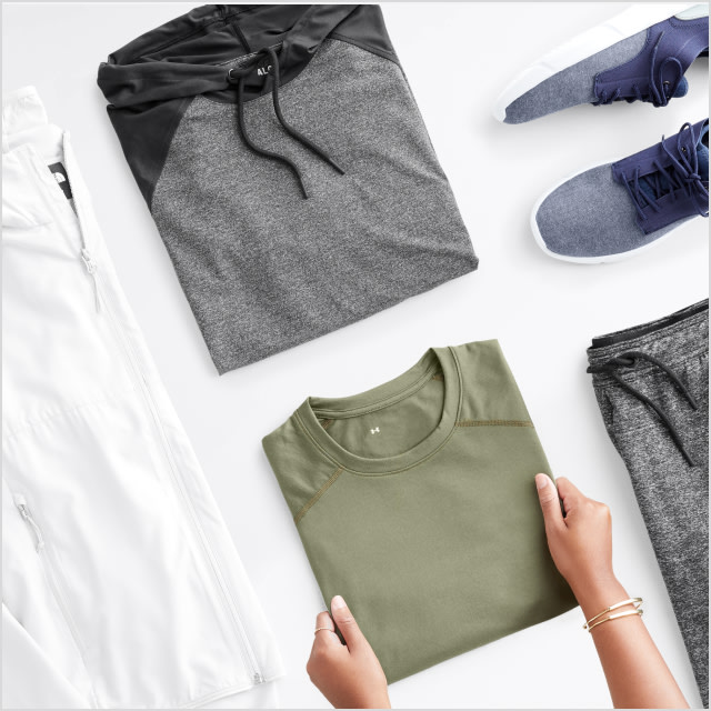 Folded Stitch Fix women's clothes including a peach top, a green floral top, a dress shirt and jeans.
