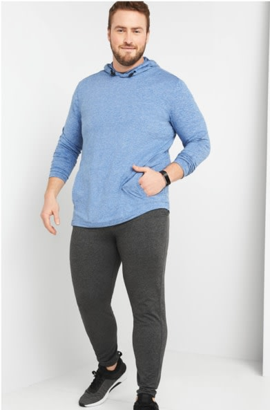 Model wearing Stitch Fix men's big and tall athleisure clothes including a blue hoodie shirt, grey sweatpants and grey sneakers.
