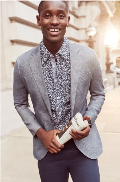 Model wearing Stitch Fix men's clothes including a black and white button shirt, grey pants.