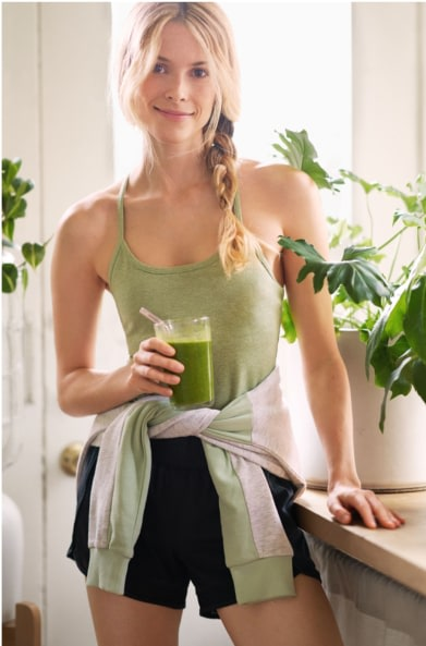 Model wearing Stitch Fix women's athleisure clothes including a green tank, black shorts and white and green jacket.
