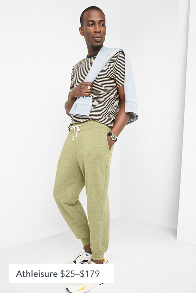 Model wearing Stitch Fix men's clothes including a striped tee, light blue sweatshirt, green jogger pants and white sneakers.