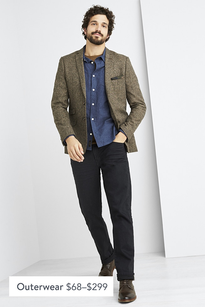 Model wearing Stitch Fix men's clothes including a blue button shirt, brown tweed blazer, black pants and black shoes.