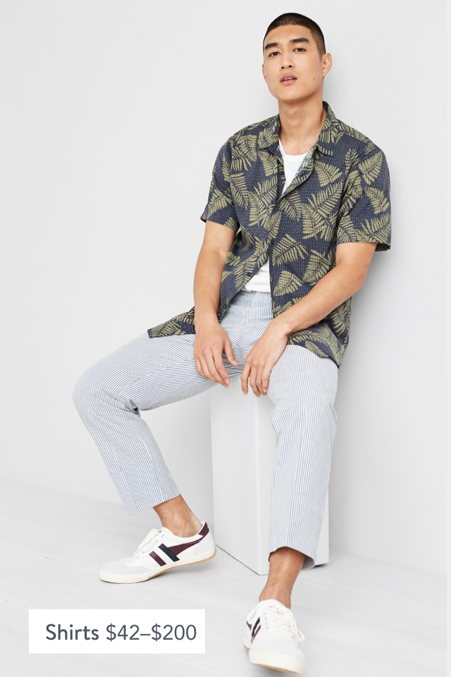 Model wearing Stitch Fix men's clothes including a blue and green Hawaiian shirt, white tee, grey pants and sneakers.