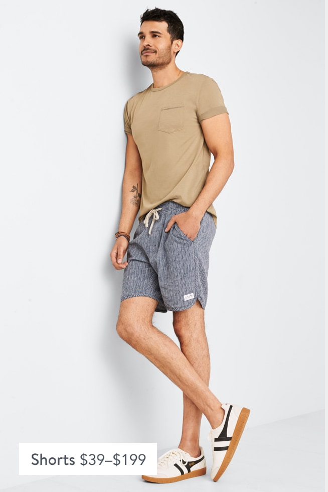 Model wearing Stitch Fix men's clothes including a tan tee, grey shorts and white sneakers.