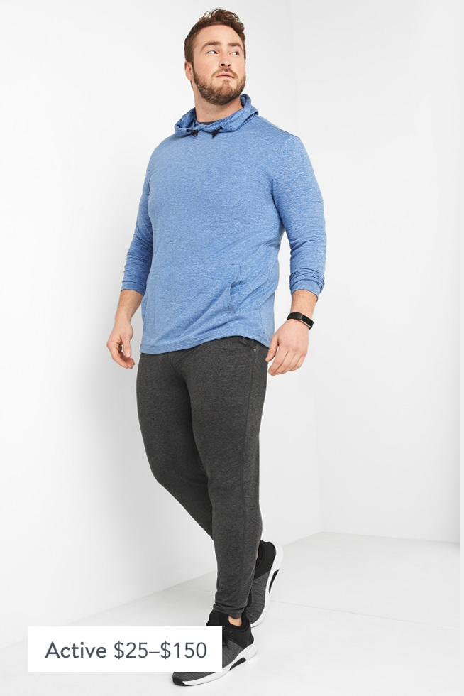 Model wearing Stitch Fix men's big and tall athleisure clothing including a blue hoodie shirt, grey sweatpants and grey sneakers.