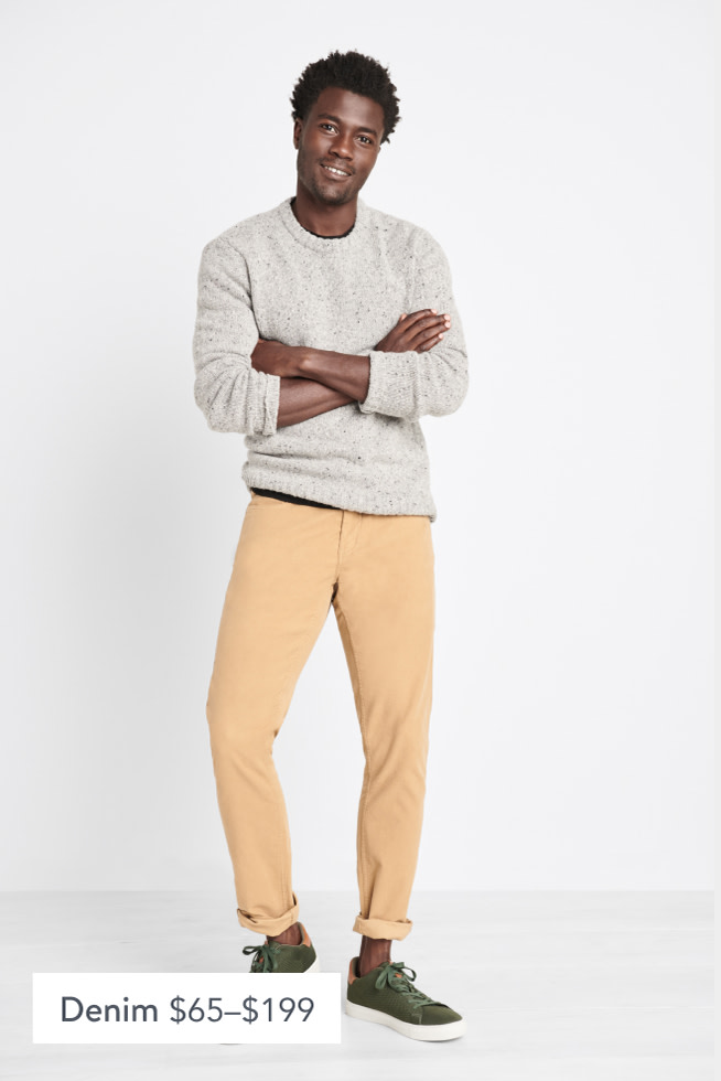 Model wearing Stitch Fix men's clothes including a grey sweater, tan pants and green sneakers.