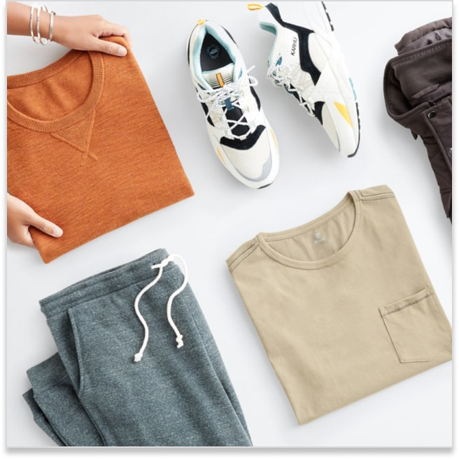Stitch Fix men's athleisure clothes including an orange sweatshirt, white sneakers, tan tee and grey jogger pants.