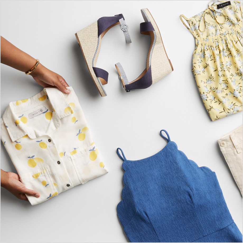 Folded Stitch Fix women's clothes including yellow and white tops, blue tank and blue sandals.
