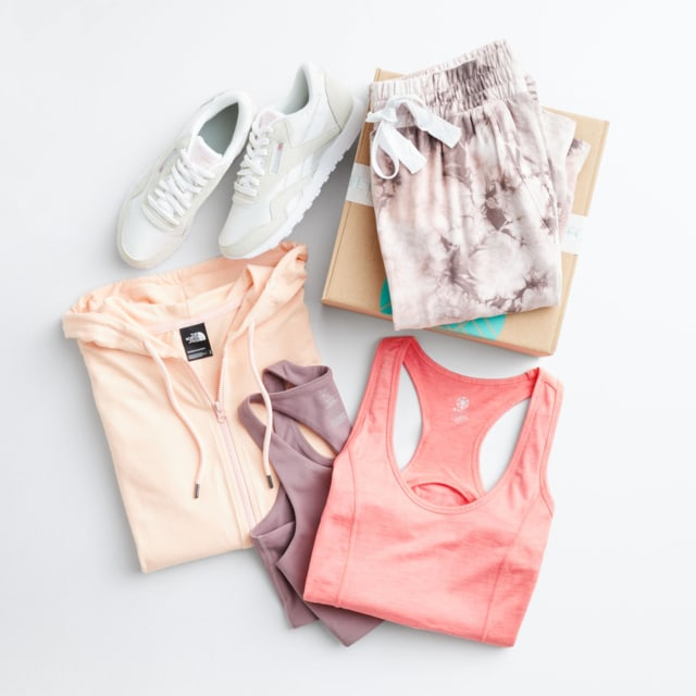 Folded Stitch Fix women's clothes including athleisure tops, a pink floral ruffle top and white sneakers.