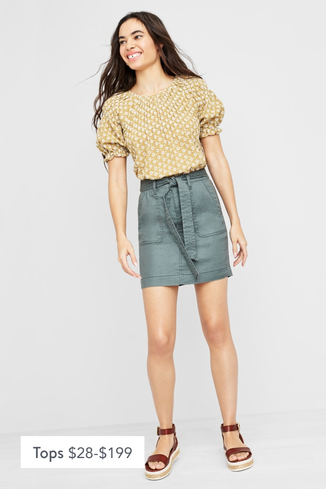 Model wearing Stitch Fix women's clothes including a beige puff sleeve top, denim skirt and brown sandals.
