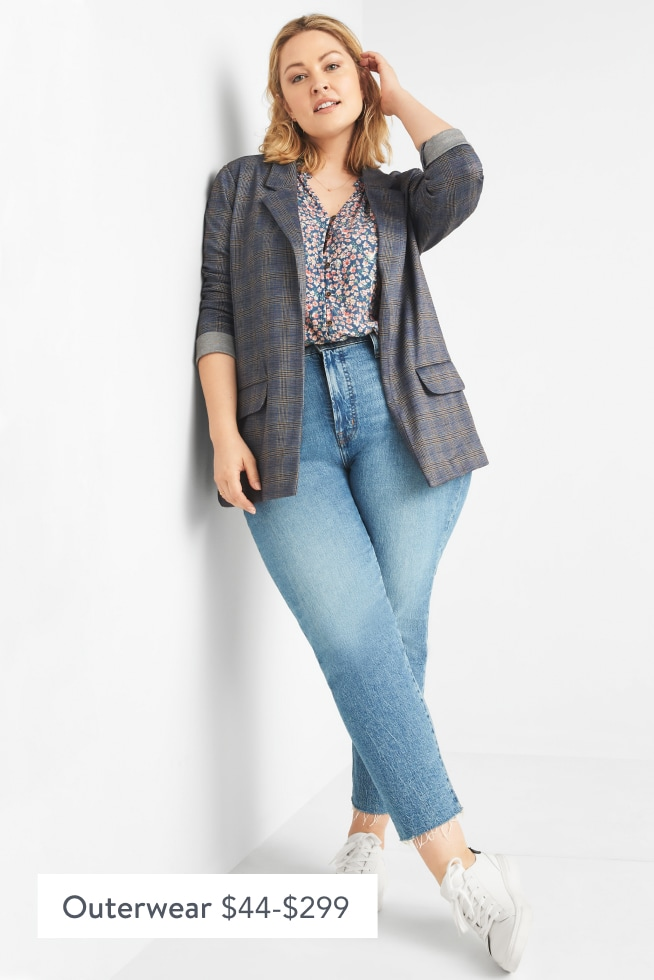 Model wearing Stitch Fix women's clothes including a floral blouse, plaid blazer, jeans and white sneakers.