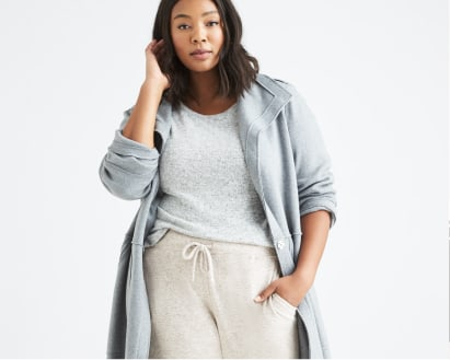 Model wearing Stitch Fix women's plus-size clothing including a grey top, grey duster sweater and grey sweatpants.