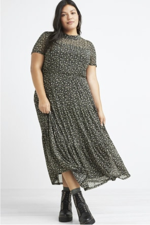 Model wearing Stitch Fix women's plus-size clothing including a grey and white floral dress and black boots.