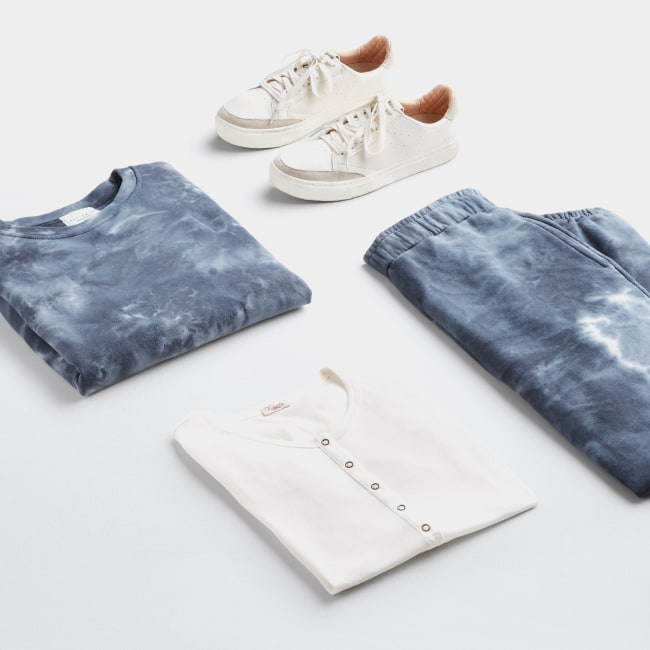 Folded Stitch Fix women's plus-size athleisure clothing including blue tie-dye pants and shirt set, white shirt and white shoes.