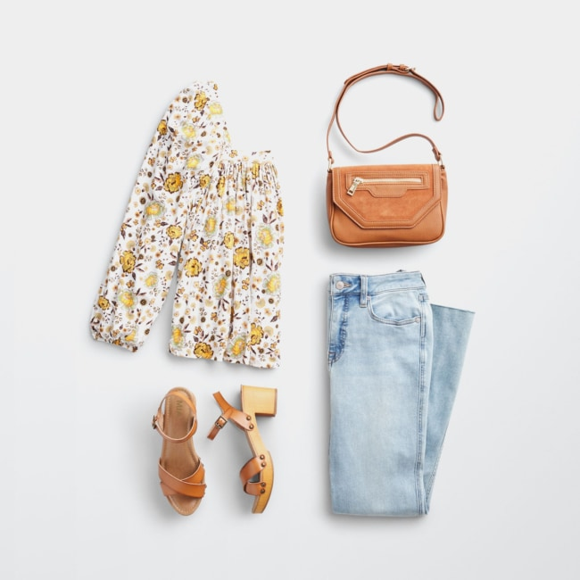 Folded Stitch Fix women's plus-size clothing including a white and yellow floral top, light wash jeans, brown handbag and sandals