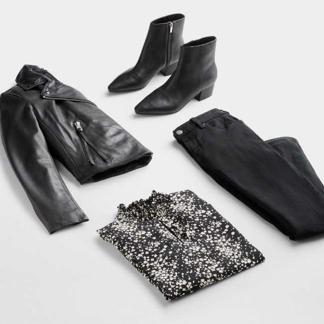 Folded Stitch Fix women's plus-size clothing including black leather jacket, booties, pants and black and white printed blouse.