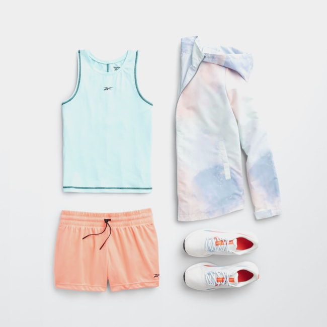Folded Stitch Fix women's plus-size athleisure clothing including blue tank top, pastel running jacket, peach shorts and white sneakers.