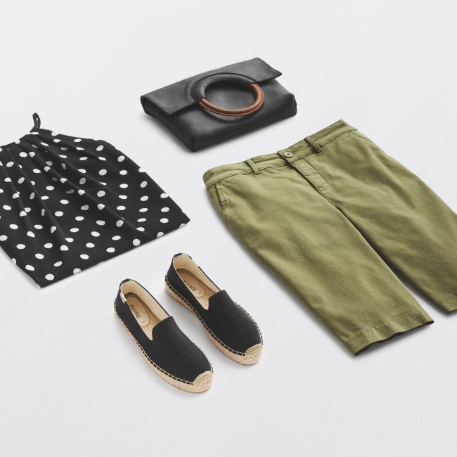 Folded Stitch Fix women's plus-size clothing including black polka dot top, black handbag, green shorts and black shoes.
