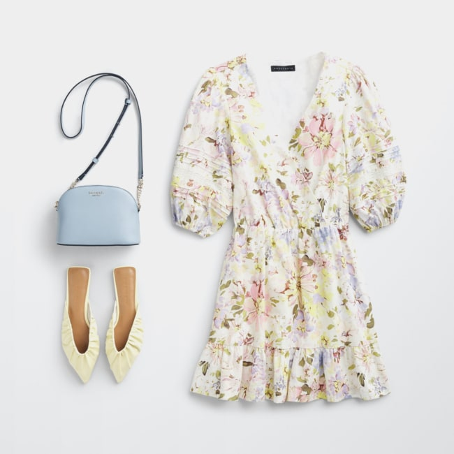 Folded Stitch Fix women's plus-size clothing including floral dress, blue crossbody bag and white mule shoes.