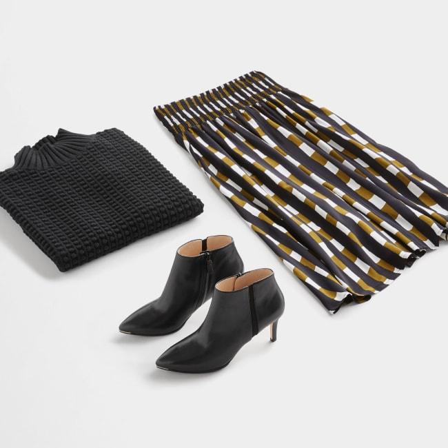 Folded Stitch Fix women's plus-size clothing including brown and white plaid skirt, black shirt and black booties.