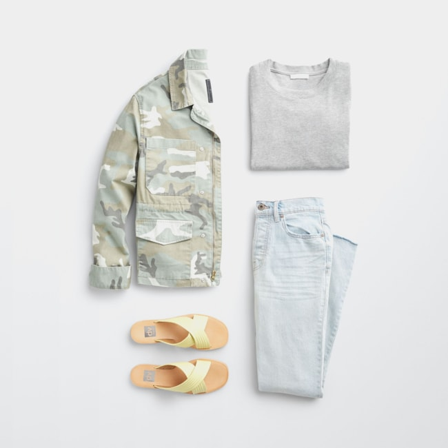Folded Stitch Fix women's plus-size clothing including camo jacket, grey shirt, light wash jeans and white sandals.