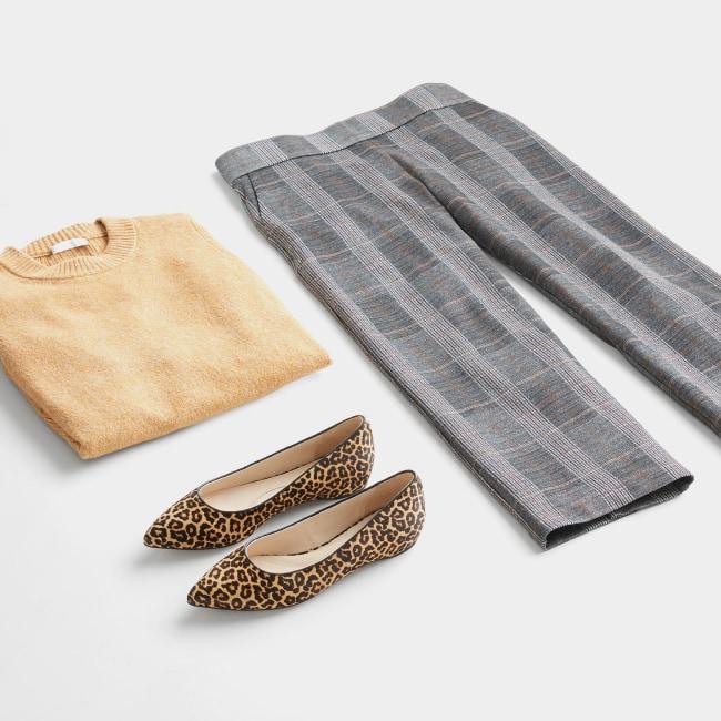 Folded Stitch Fix women's plus-size clothing including tan sweater, grey slacks and leopard print flats.
