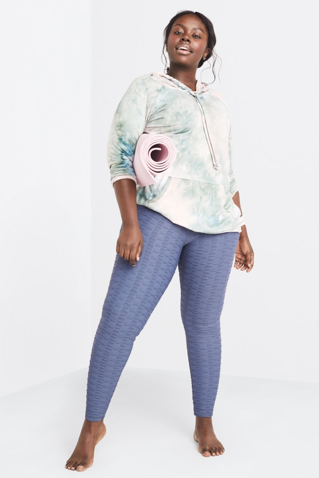 Model wearing Stitch Fix women's plus-size athleisure yoga clothing including blue leggings and printed shirt.