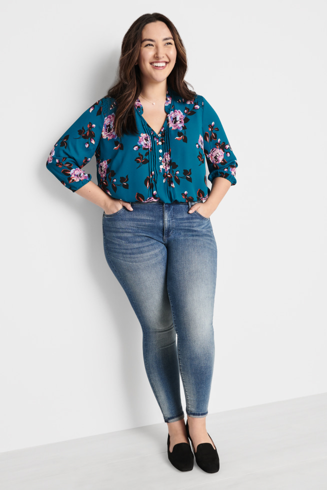 Model wearing Stitch Fix women's plus-size clothing including teal floral top, faded jeans and black shoes.