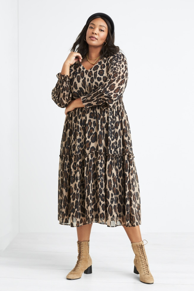 Model wearing Stitch Fix women's plus-size clothing including leopard print dress and tan lace-up booties.