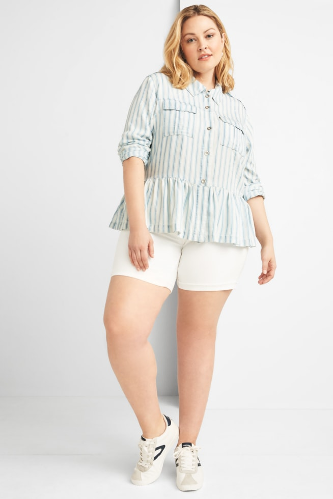Model wearing Stitch Fix women's plus-size clothing including denim top with ruffle detail, white shorts and white sneakers.