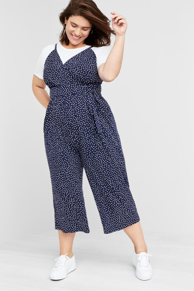 Model wearing Stitch Fix women's plus-size clothing including blue and white floral jumpsuit with whte tee and sneakers.